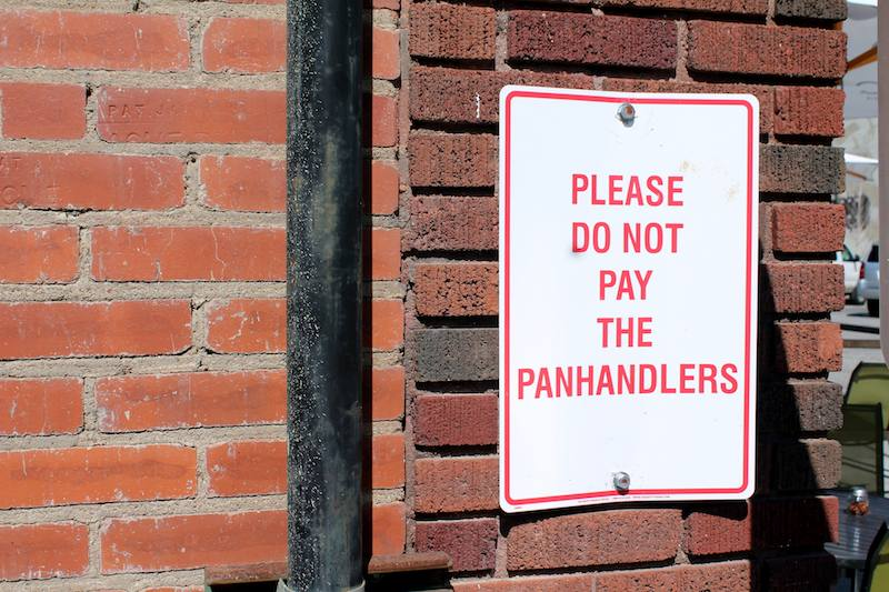 A sign posted in downtown Tulsa's Brady District instructs patrons not to pay the panhandlers, who are subject to fines and being charged with aggressive illegal begging.