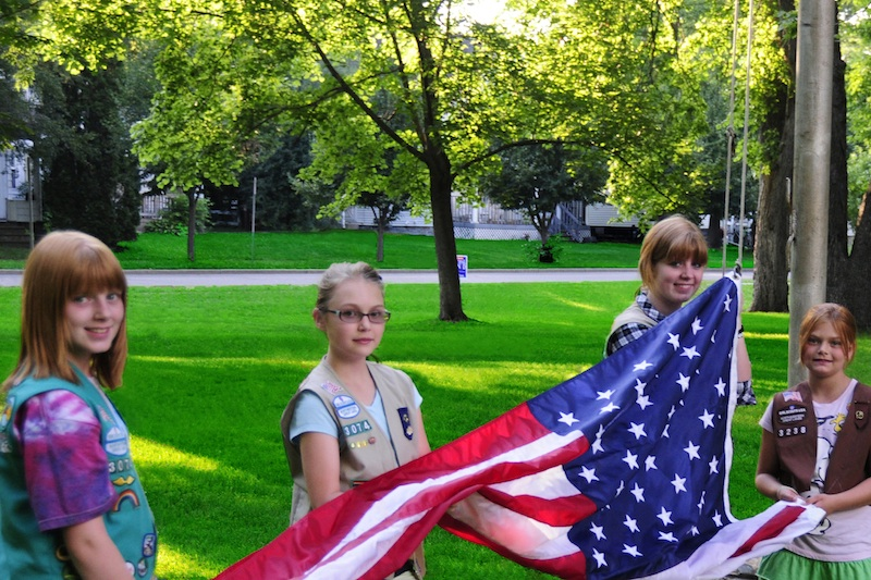 """Girl Scouts raise the American flag. The organization focuses on """"building girls of courage, confidence, and character."""""""