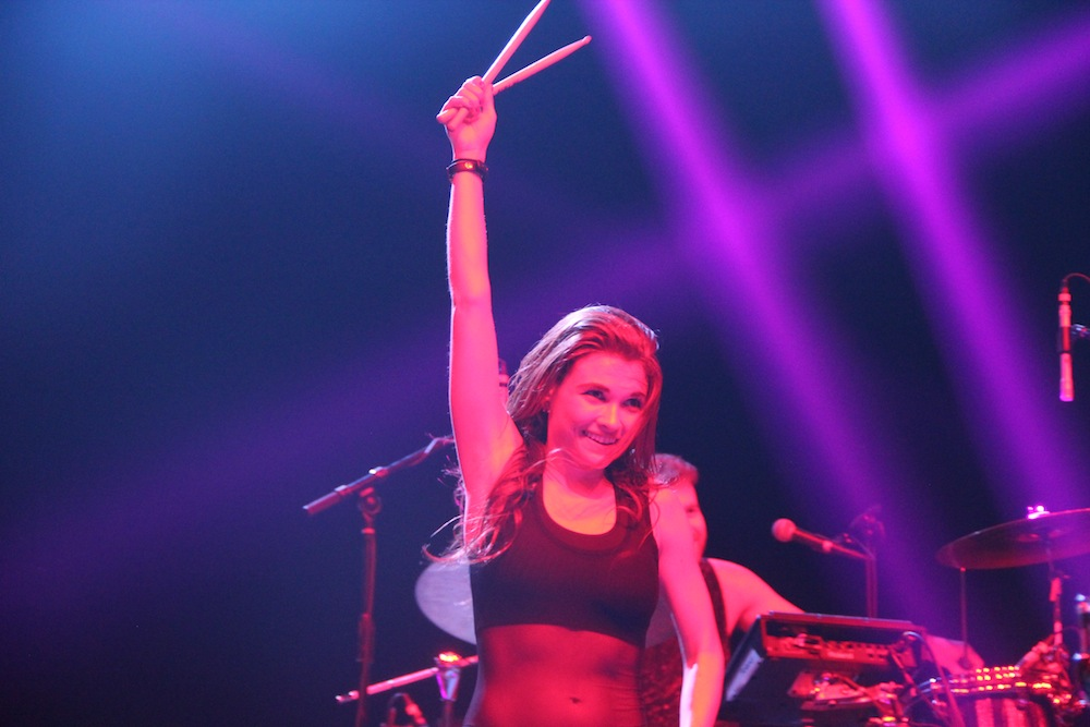 Mandy Lee raises her drumsticks triumphantly.